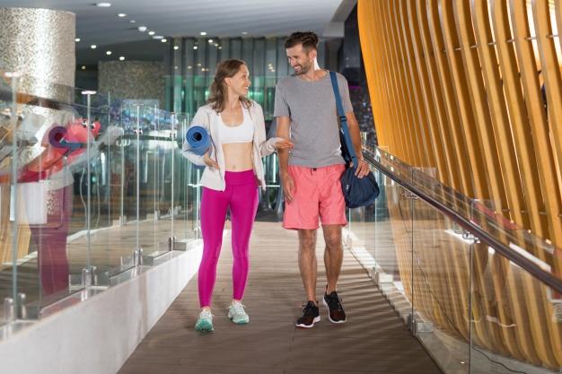 femme-et-homme-bavarder-a-la-porte-de-salle-de-gym_1262-700