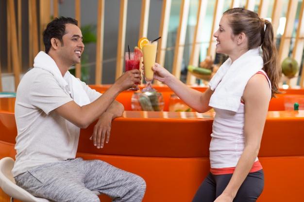 femme-et-homme-grillage-jus-de-fruits-dans-un-bar_1262-701